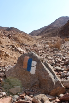 Israel National Trail marker near Eilat. The National trail runs from the Israel-Lebanon border to the Red Sea. The orange stripe represents the desert (South), and the white stripe represents snow (North). Since the orange stripe is on top, you know you're hiking south. Israel does a REALLY good job marking ALL their hiking trails.