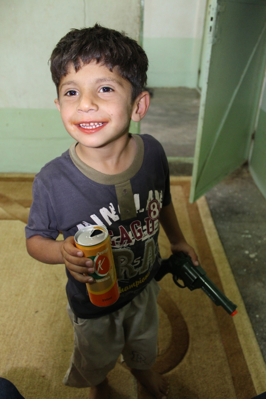 Oh, Hama is SUCH a Kurdish child. Mouth orange from a soda and holding a toy gun.